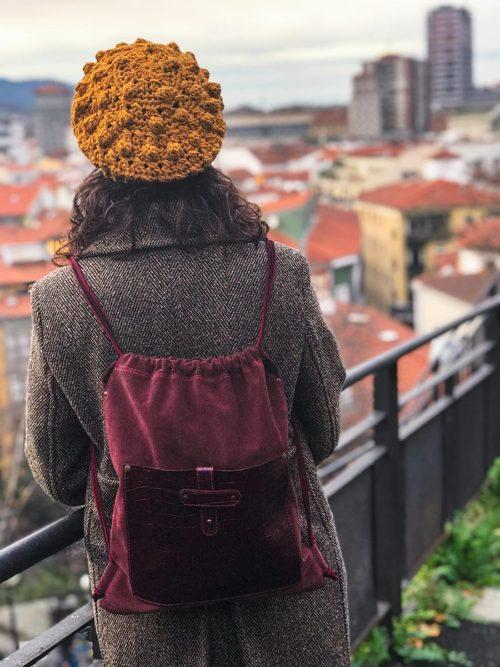 OTRORA_Mochila artesanal de piel en color burdeos con boina tejida a mano de color mostaza