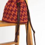 OTRORA_Bombonera de crochet y cuero estampada en pata de gallo granate y caldera