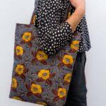Bolsa tote bag de tela estampada de flores en color mostaza con fondo gris