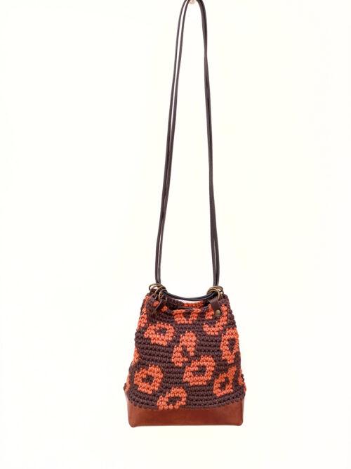 Bolso saco artesanal de crochet y cuero con estampado de leopardo en marrón y caldera. Tejido a mano con hilo de algodón reciclado y PET de botellas recicladas. Base de piel vacuno de curtición vegetal.