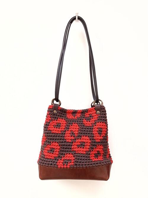 Bolso saco artesanal de crochet y cuero con estampado de leopardo en marrón y rojo. Tejido a mano con hilo de algodón reciclado y PET de botellas recicladas. Base de piel vacuno de curtición vegetal.