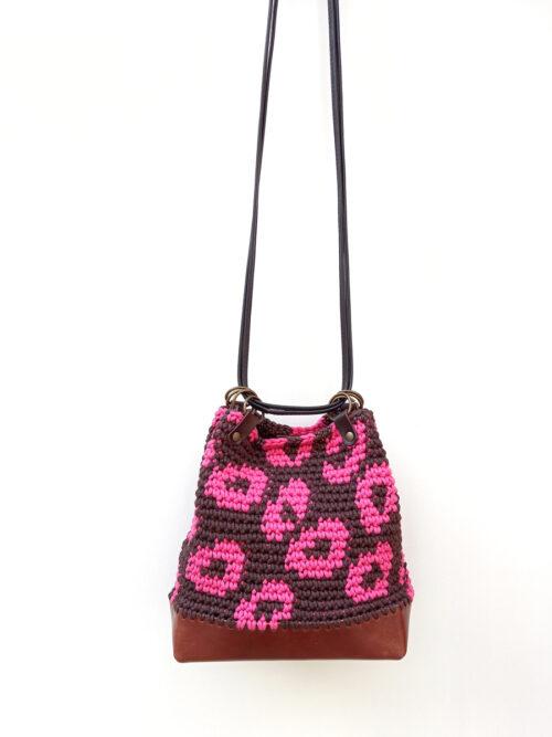 Bolso saco artesanal de crochet y cuero con estampado de leopardo en marrón y rosa. Tejido a mano con hilo de algodón reciclado y PET de botellas recicladas. Base de piel vacuno de curtición vegetal.